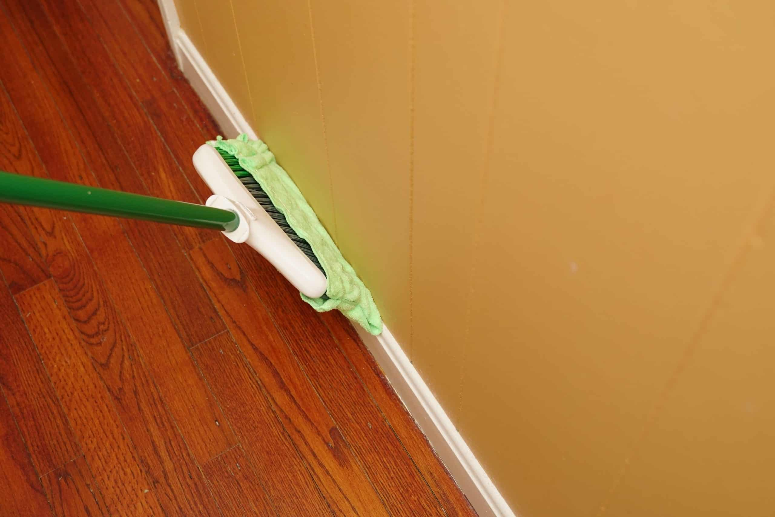 Cleaning baseboards with broom
