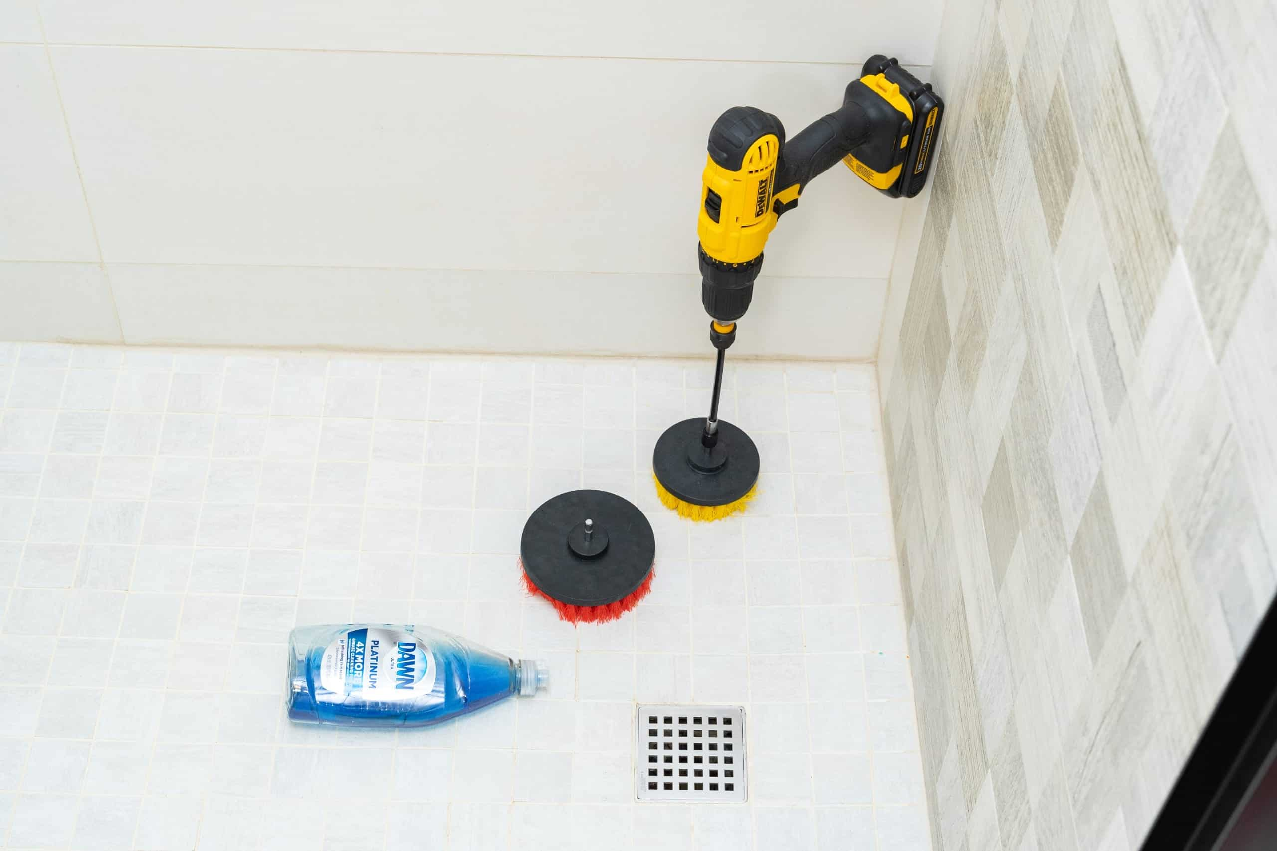 using brush to clean shower tile